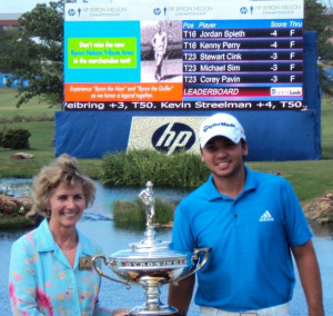 Jason Day with Mrs. Peggy Nelson with Byron in the background on the scoreboard after Day's historic first win!