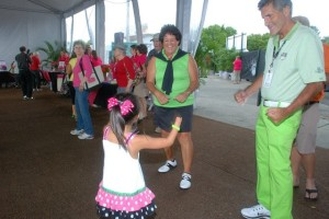 Clothing color-coordinated Saggy dancing with Nancy Lopez and a young girl.