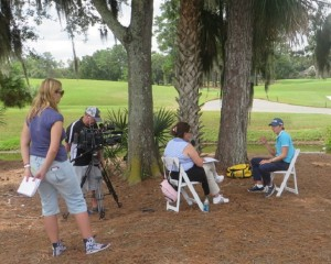 Carlos Ortiz doing a media interview in the shade near the TOUR Academy.