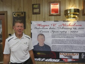 Snowmobile Hall of Fame member Wayne Nicholsen in front of a tribute area in Armae Hall at Sunny Hill.