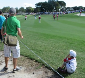 Little Rory (sitting) with dad Kevin (green shirt) watching Big Rory hit his approach shot into the 17th green.