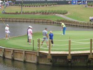 Tebow brothers on the 17th green. Robby putting Kaymer putt with Tim watching. Both are good golfers.
