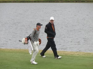 "Texas Assistant Coach Jean-Paul ""J.P."" Hebert walking up the 18th fairway with Gavin Hall."