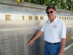 Dennis Berkholtz pointing to the 1996 Handball Olympic Team at the Olympic Torch Park.