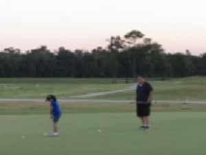 A father and a daughter having fun putting at the David Shindeldecker First Tee Campus.
