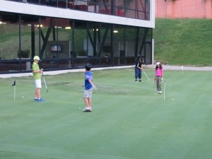 Kids, Gabriel, Kevin & Jasmine outnumber the adult 3-to-1 on the practice putting green at Top Tee Cayala.