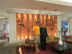 """In the lobby of the Intercontinental Real San Salvador with Bellhop Fernando in front of Fernando Llort's """"The Story of My People."""""""